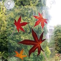 Vallende herfstblaadjes voor het raam