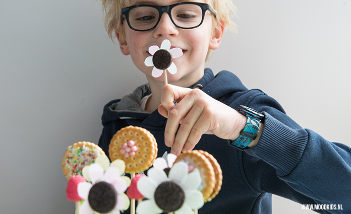 Dit zoete bloementuintje van koekbloemetjes is een leuke traktatie voor je kind. Je kind kan gezellig mee helpen. Lees hier stap voor stap hoe je ze maakt.